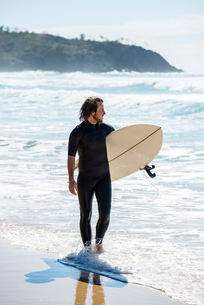 Australia, Queensland, Sunshine Coast, Noosa, Alexandria Bay, Surfer with surfboard walking on sandの写真素材 [FYI02855610]