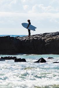 Australia, Queensland, Sunshine Coast, Noosa, Alexandria Bay, Young man holding surfboard on beachの写真素材 [FYI02855611]