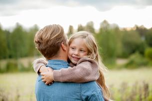 Finland, Uusimaa, Raasepori, Karjaa, Young girl (6-7) hugging her fatherの写真素材 [FYI02855624]