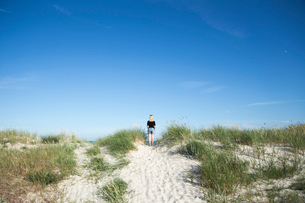 Sweden, Skane, Soderslatt, Beddinge, Rear view of blonde woman standing on beach and looking at seaの写真素材 [FYI02855625]