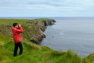 United Kingdom, Scotland, Shetland Islands, Unst, Senior woman standing at grassy cliff looking throの写真素材 [FYI02855626]