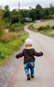 Finland, Uusimaa, Raasepori, Karjaa, Baby boy (12-17 months) walking country roadの写真素材 [FYI02855639]