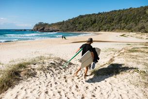 Australia, Queensland, Sunshine Coast, Noosa, Alexandria Bay, Young man carrying surfboards on beachの写真素材 [FYI02855646]