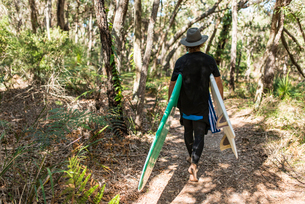 Australia, Queensland, Sunshine Coast, Noosa, Alexandria Bay, Young man carrying surfboardの写真素材 [FYI02855658]