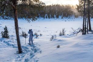 Sweden, Vasterbotten, Tarnaby, Goose hunter (16-17) in winter forestの写真素材 [FYI02855661]