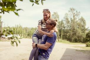 Sweden, Skane, Ostra Goinge, Man carrying girlfriendの写真素材 [FYI02855685]
