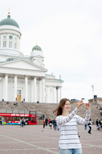Finland, Uusimaa, Helsinki, Senaatintori, Young woman photographing self with Lutheran Cathedral inの写真素材 [FYI02855699]