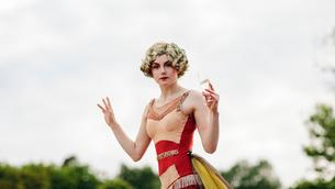 Sweden, Uppland, Hagaparken, Woman acrobat holding glass of champagneの写真素材 [FYI02855705]