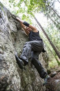 Sweden, Sodermanland, Tyreso, Sportsman doing bouldering in forestの写真素材 [FYI02855741]