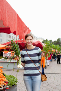 Finland, Uusimaa, Helsinki, Kauppatori, Portrait of smiling woman holding vegetables at street markeの写真素材 [FYI02855755]