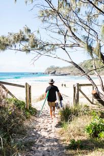 Australia, Queensland, Sunshine Coast, Noosa, Alexandria Bay, Young man carrying surfboardの写真素材 [FYI02855763]