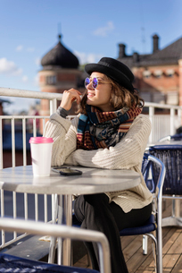 Sweden, Vasterbotten, Umea,  Young woman sitting at sidewalk cafeの写真素材 [FYI02855768]