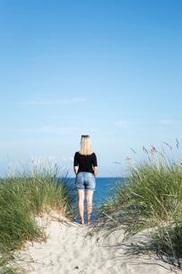 Sweden, Skane, Soderslatt, Beddinge, Rear view of blonde woman standing on beach and looking at seaの写真素材 [FYI02855769]