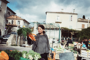 France, Languedoc-Roussillon, Sauve, Young tourist looking at carrot on marketの写真素材 [FYI02855771]
