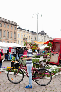 Finland, Uusimaa, Helsinki, Kauppatori, Portrait of smiling young woman with bicycle at street markeの写真素材 [FYI02855775]