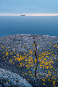 Sweden, Stockholm archipelago, Sodermanland, Femore, Eroded rock with water in backgroundの写真素材 [FYI02855779]
