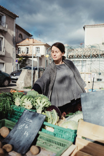 France, Languedoc-Roussillon, Sauve, Young tourist choosing vegetables on marketの写真素材 [FYI02855808]