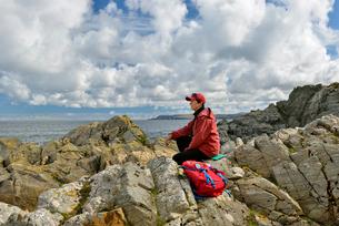 UK, Scotland, Shetland, Yell, Otterswick, Senior woman sitting on rockの写真素材 [FYI02855838]
