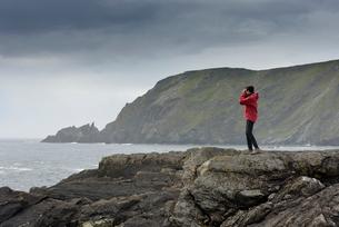 UK, Scotland, Shetland, Garth's Ness, Senior woman standing on rock, looking at viewの写真素材 [FYI02855846]