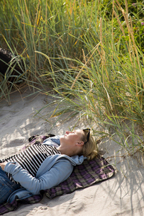 Sweden, Skane, Soderslatt, Beddinge, High angle view of blonde woman resting on sand next to growingの写真素材 [FYI02855851]