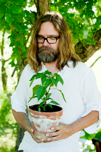 Sweden, Sodermanland, Man standing with eyes closed holding potted plantの写真素材 [FYI02855853]