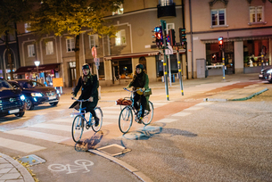 Sweden, Uppland, Stockholm, Vasatan, Sankt Eriksgatan, Man and woman cycling on city streetの写真素材 [FYI02855863]