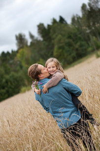 Finland, Uusimaa, Raasepori, Karjaa, Father kissing his daughter (6-7) on cheekの写真素材 [FYI02855868]