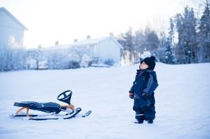 Sweden, Uppland, Racksta, Young boy (2-3) standing on snowの写真素材 [FYI02855881]