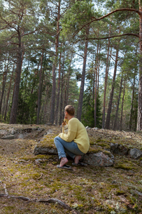 Sweden, Sodermanland, Stockholm County, Nacka, Mid adult woman with dog resting in forestの写真素材 [FYI02855884]