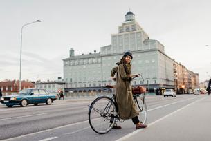 Sweden, Uppland, Stockholm, Vasatan, Sankt Eriksgatan, Woman cycling on city streetの写真素材 [FYI02855887]