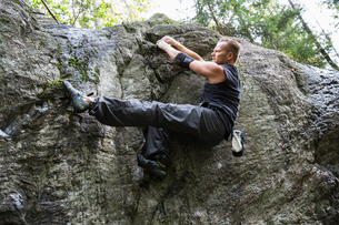 Sweden, Sodermanland, Tyreso, Sportsman doing bouldering in forestの写真素材 [FYI02855894]