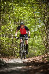 Sweden, Blekinge, Solvesborg, Ryssberget, Mature man riding on mountain bike through forestの写真素材 [FYI02855915]