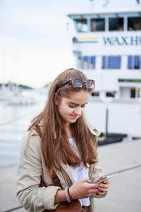 Sweden, Stockholm Archipelago, Sodermanland, Uto, Teenage girl (14-15) using smart phoneの写真素材 [FYI02855917]