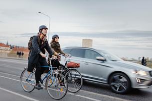Sweden, Uppland, Stockholm, Vasatan, Sankt Eriksgatan, Man and woman cycling on city streetの写真素材 [FYI02855926]
