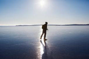 Sweden, Sodermanland, Mysingen, Silhouette of man ice-skating on frozen seaの写真素材 [FYI02855932]