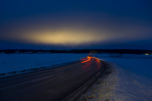 Sweden, Sodermanland, Skavsta, Light trail on road in winter at duskの写真素材 [FYI02855936]