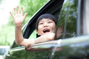 Cheerful boy waving out of car windowの写真素材 [FYI02855962]