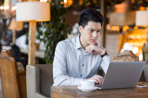 Young man using laptop in cafeの写真素材 [FYI02855969]