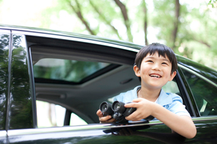 Cheerful boy leaning out of car window with binoculars in haの写真素材 [FYI02855970]