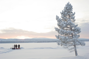 Sweden, Lappland, Jokkmokk, Three men in field in winterの写真素材 [FYI02856013]