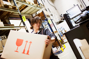 Sweden, Young woman working in warehouseの写真素材 [FYI02856049]