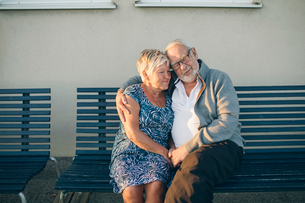Senior couple hugging on benchの写真素材 [FYI02856070]