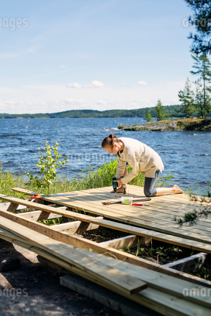 Mid adult woman building a deck in front of a lake in Finlandの写真素材 [FYI02856081]