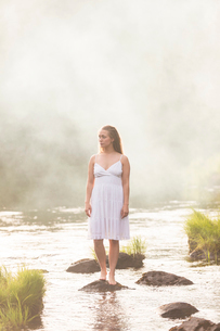 Woman wearing a white dress standing in riverの写真素材 [FYI02856099]