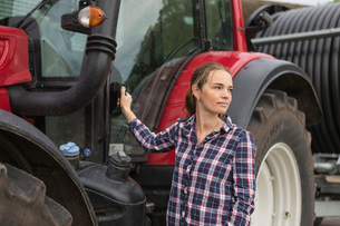 Agricultural worker standing next to a tractor in fieldの写真素材 [FYI02856115]