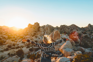 USA, California, Woman spreading arms in Joshua Tree National Parkの写真素材 [FYI02856120]