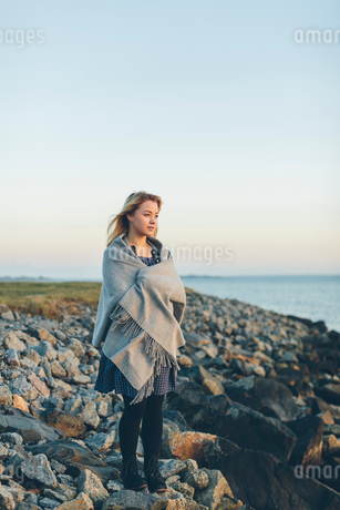 A young woman wrapped in a shawl looking out to seaの写真素材 [FYI02856133]