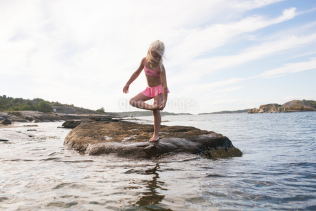 Sweden, Vastra Gotaland, Koster Islands, Girl (6-7) standing on rock in seaの写真素材 [FYI02856147]
