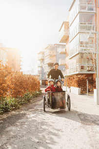 Man cycling with his sons in Stockholmの写真素材 [FYI02856150]