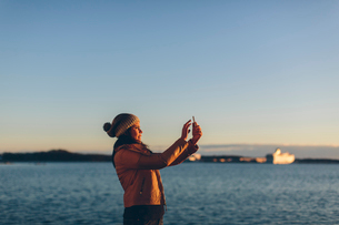 Woman holding a smart phone by the seaの写真素材 [FYI02856155]
